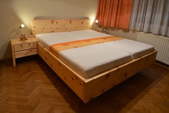 Schlafzimmer_Bett-aus-massivem-Zirbenholz-schwebende-Optik-mit-Nachtkaestchen